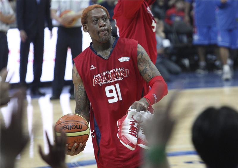 En la imagen, el exjugador de la NBA Scottie Pippen Dennis Rodman lanza un balón autografiado al público durante un partido de exhibición