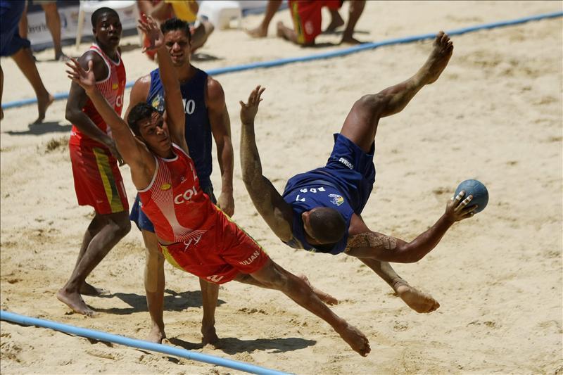 Julian Villa (i) de Colombia intenta bloquear a Thiago Gusmao de Brasil (d) el 3 de agosto de 2013, durante la competencia masculina de Balonmano Playa en la novena versión de los Juegos Mundiales, en la ciudad de Cali (Colombia). EFE
