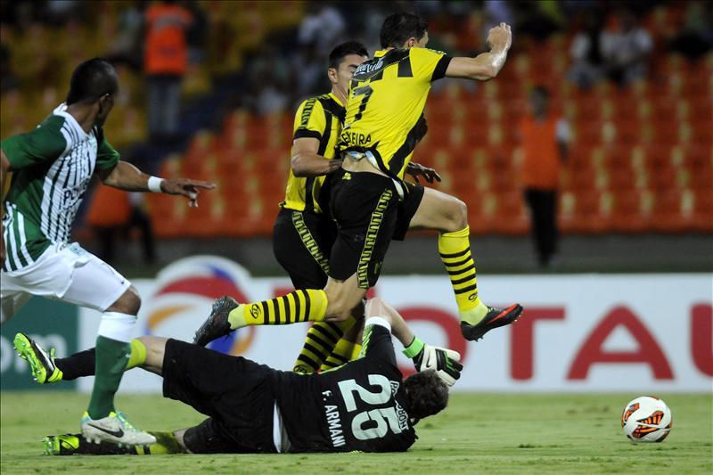 El arquero de Atlético Nacional Franco Armani (abajo) disputa el balón con los jugadores Rodrigo Teixeira (d) y Miguel Paniagua (c-d) de Guaraní de Paraguay, durante el partido de la Copa Sudamericana disputado en Medellín (Colombia). EFE
