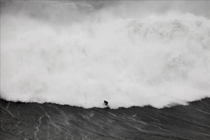 El brasileño Burle toma una ola gigante, mientras su compatriota Maya da un susto. EFE.