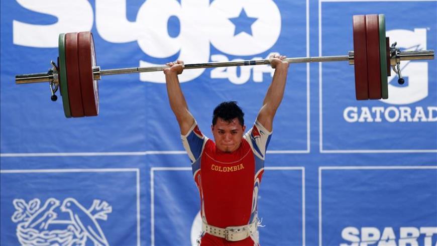 Carlos Berna de Colombia, medalla de oro, compite en la categoría masculina 56kg. de levantamiento de pesas. EFE