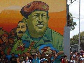 Un grupo de jóvenes posa junto a un mural del que fuera presidente de Venezuela, Hugo Chávez. EFE/Archivo