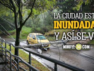 Que impresion Por fuertes lluvias en Bogota poste cayo encima de un taxi