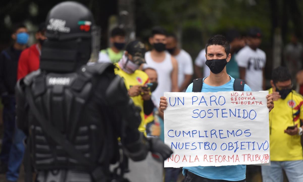 Un hombre sostiene ayer un cartel contra la reforma tributaria que impulsa el Gobierno de Iván Duque, mientras un efectivo del Escuadrón Móvil Antidisturbios (ESMAD) lo vigila, durante una protesta en Cali (Colombia). EFE/ Ernesto Guzmán Jr Defensa