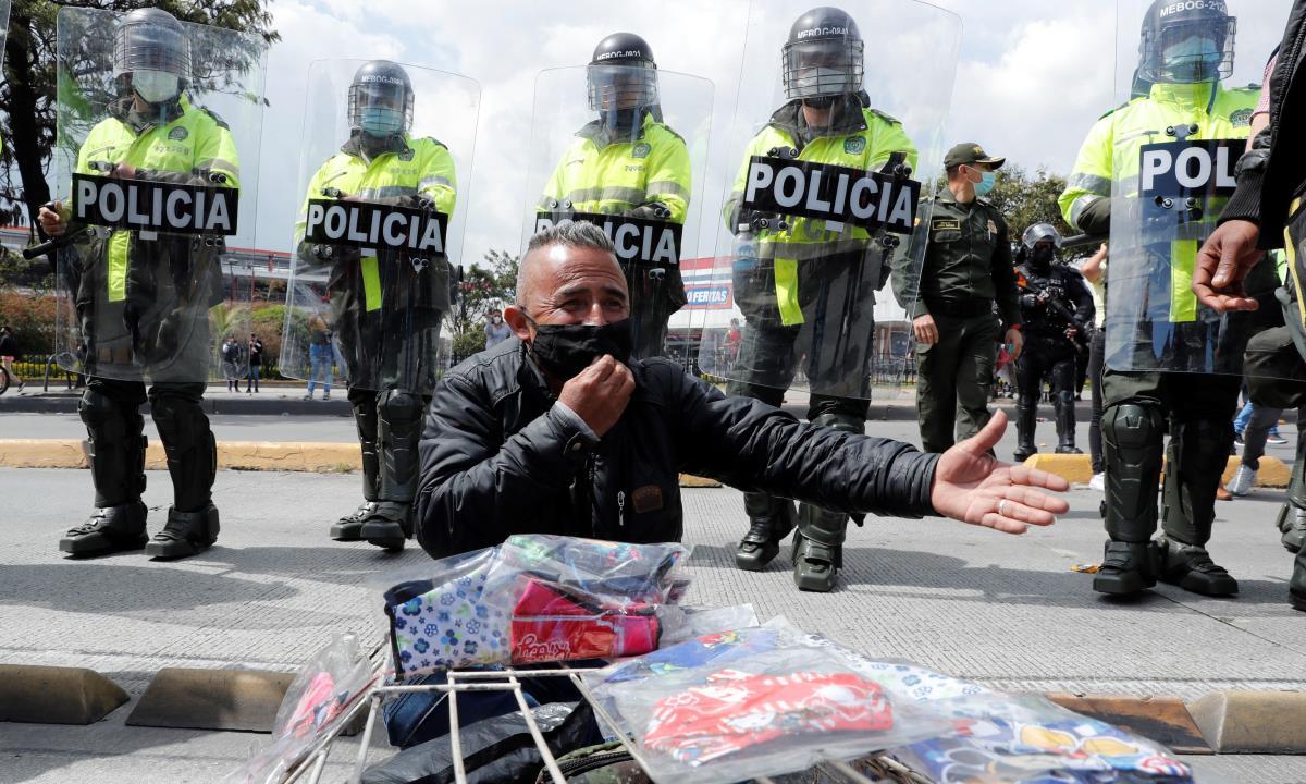 Efectivos de la Policía de Colombia fueron registrados este viernes al vigilar una vía bloqueada, en protesta por un nuevo confinamiento para contener la expansión de la covid-19, en Bogotá (Colombia). EFE/Mauricio Dueñas Castañeda