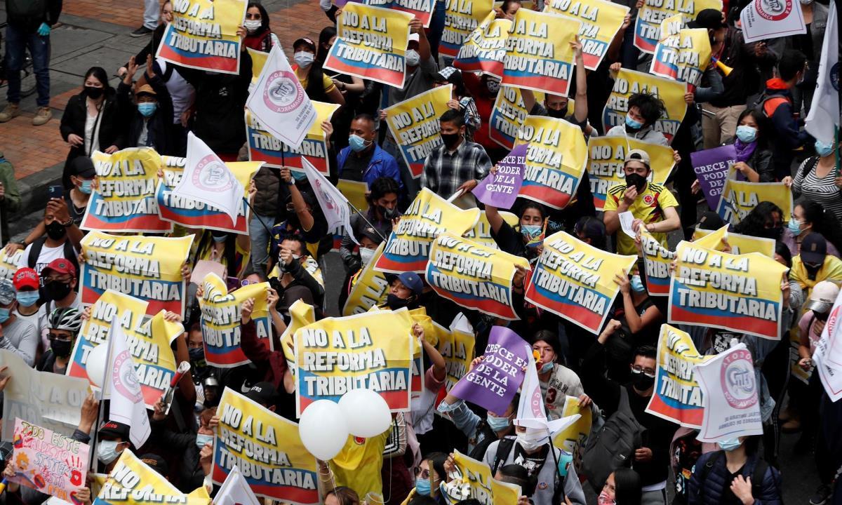 Decenas de personas entre las que sobresalen carteles de protesta participa en la jornada de manifestaciones denominada Paro Nacional, convocada en todo el país para rechazar, entre otros, la reforma tributaria del Gobierno hoy, en Bogotá (Colombia). EFE/ Carlos Ortega