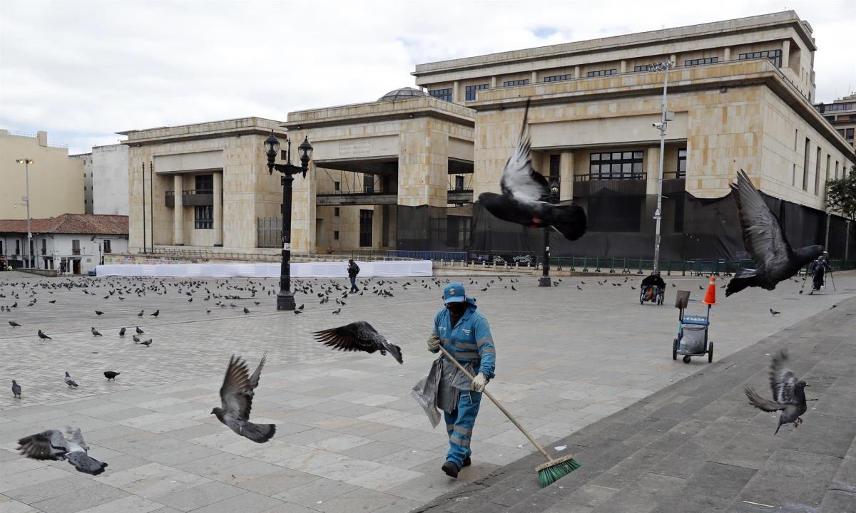 Un trabajador sanitario limpia una casi vacía Plaza de Bolívar, en Bogotá (Colombia). EFE/ Mauricio Dueñas Castañeda/Archivo
