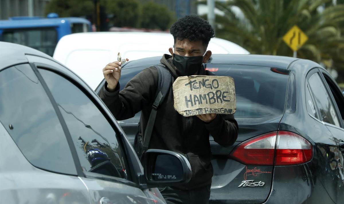 Un hombre vende dulces y pide ayuda en un semáforo en Bogotá (Colombia). EFE/ Mauricio Duenas Castañeda/Archivo