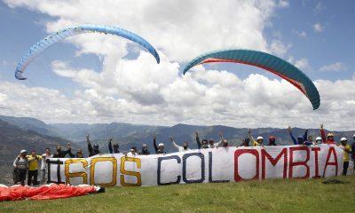 """Varios pilotos de parapente posan con una pancarta en la que se lee """"SOSColombia"""" al final de una actividad que denominaron """"marcha aérea"""" hoy, sobre el corregimiento de San Félix, en Antioquia (Colombia). EFE/ Luis Eduardo Noriega A."""
