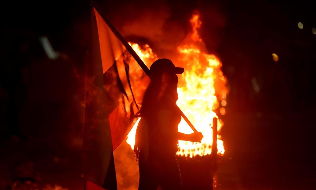 Fotografía del 3 de mayo de 2021 que muestra a un grupo de manifestantes que incendian llantas mientras bloquean vías durante las protestas en Cali (Colombia). EFE/ Ernesto Guzmán Jr