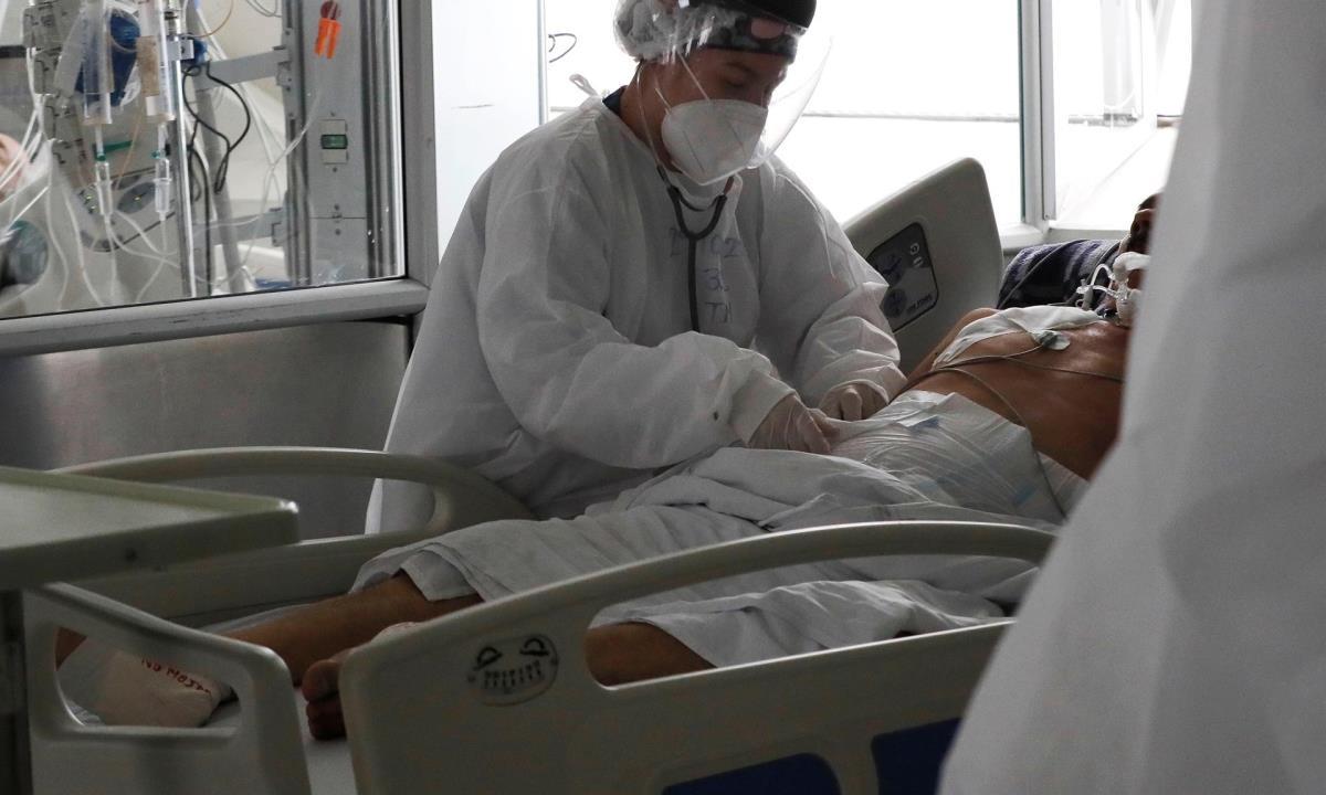 Una empleada de la salud atiende a un paciente en una unidad de cuidados intensivos para enfermos de covid-19 en el Hospital El Tunal, el 30 de abril de 2021 en Bogotá (Colombia). EFE/Carlos Ortega