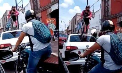mujer cicla encima carro via