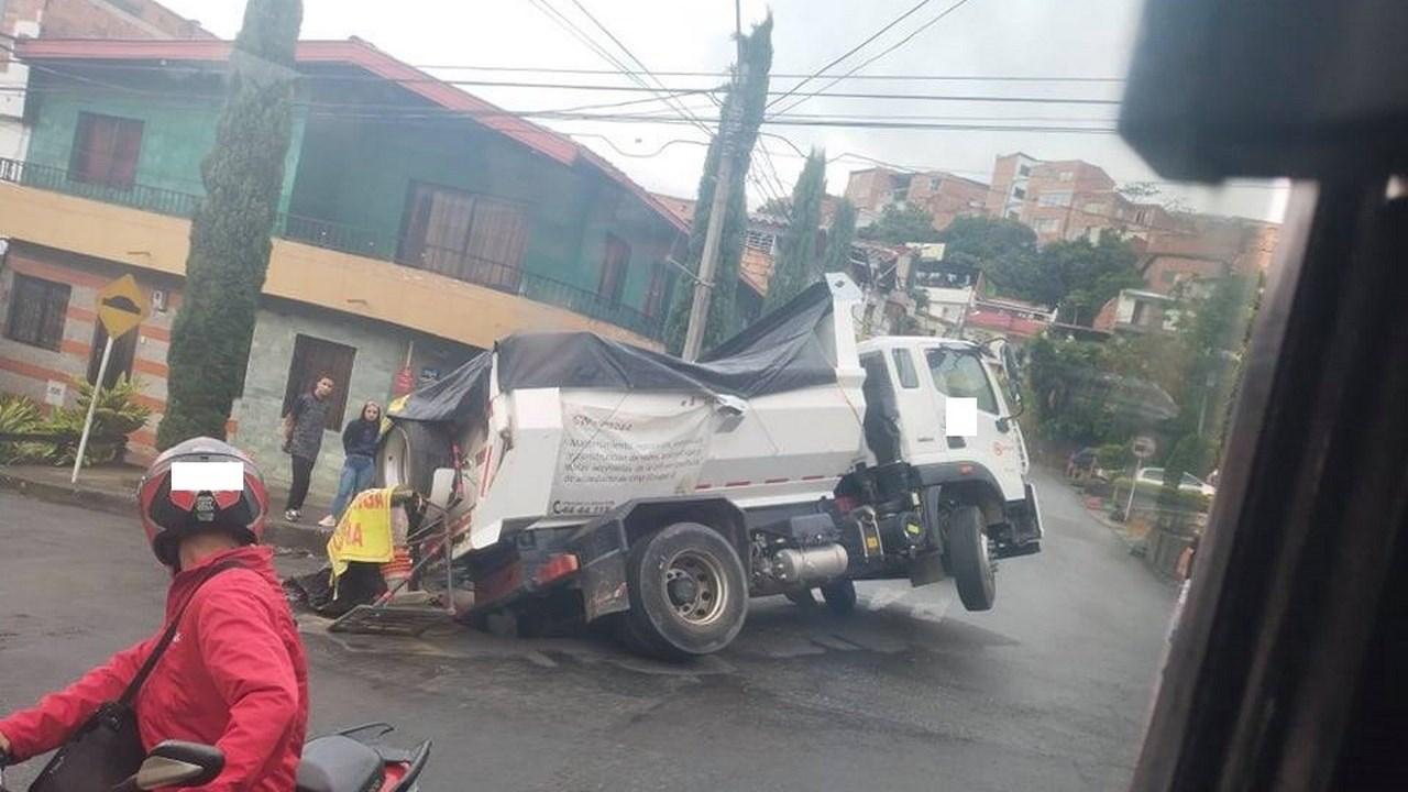 Se abrió la calle, volqueta quedó atrapada en un hueco en San Javier La Pradera - Noticias de Colombia